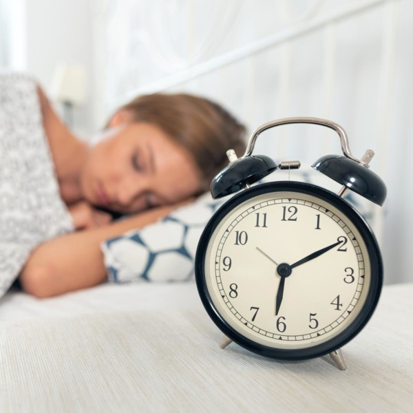 Image of an alarm clock next to someone sleeping.