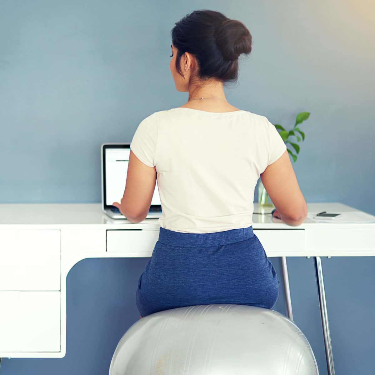 Image of someone sitting on a medicine ball chair at their desk.