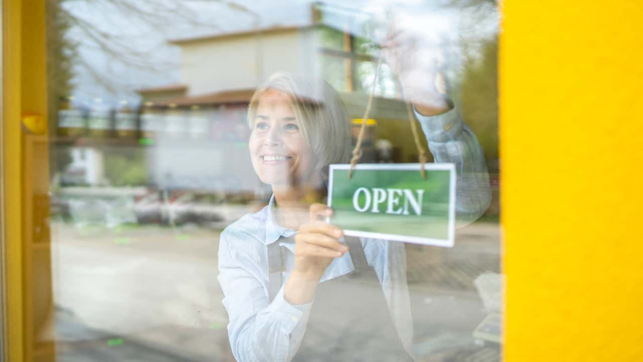 Image of someone hanging an 'open' sign on their door.