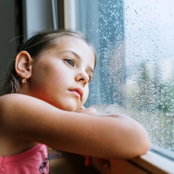 child looking longingly into a window with rain droplets