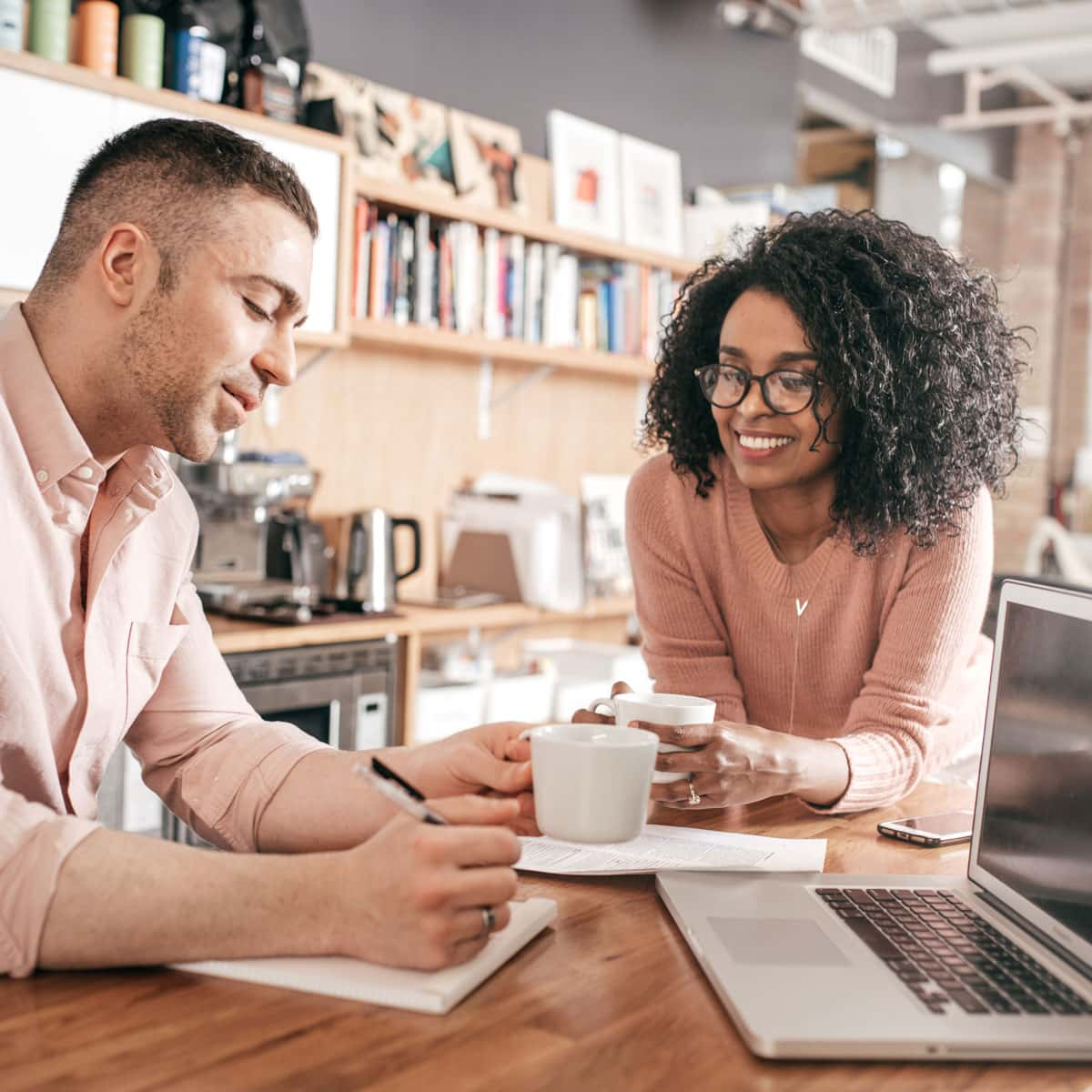Couple drinking coffee and looking over the costs of a new home