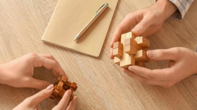 Image of people holding cube shaped puzzles.