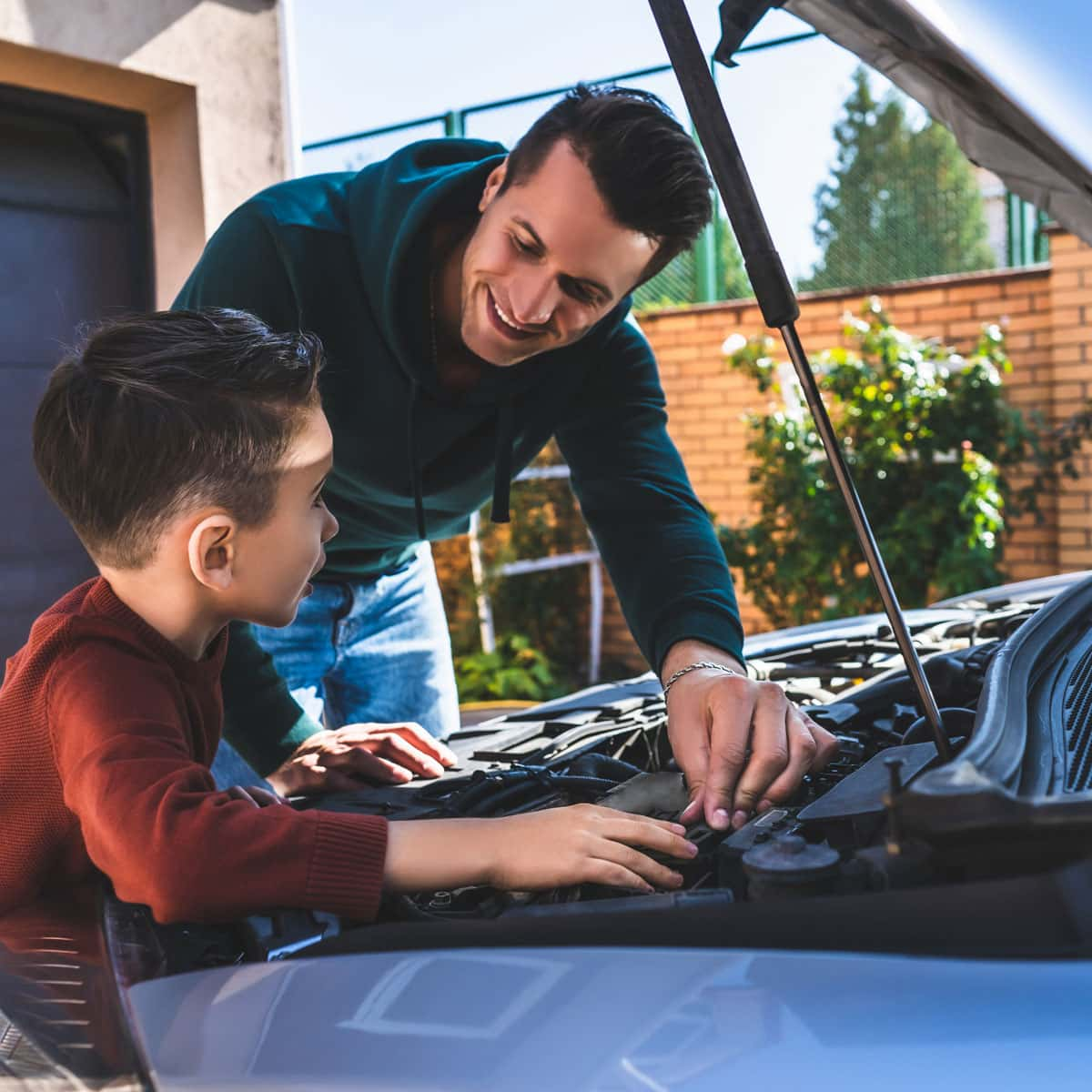 man showing son how to fix a car