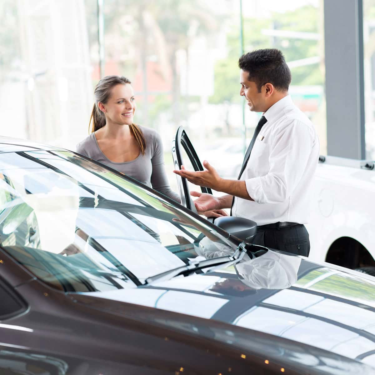 Image of a sales person with a customer looking at a car in a dealership.