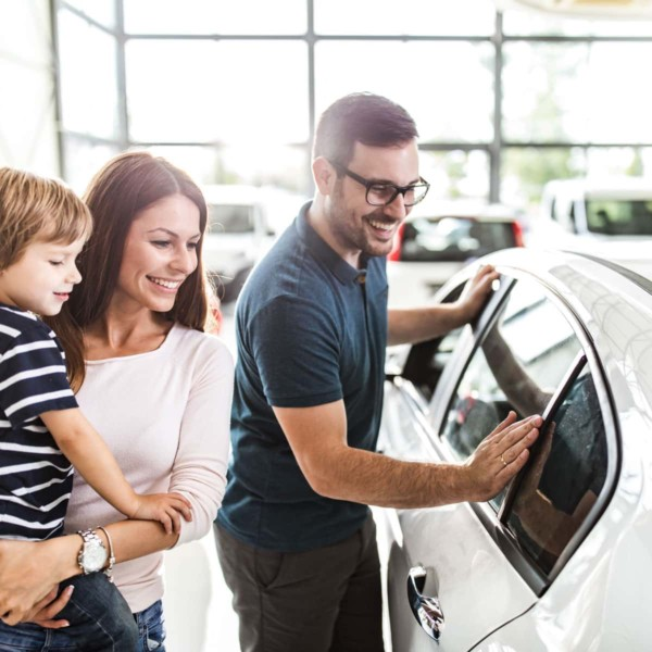 Image of people looking at a car in a dealership.