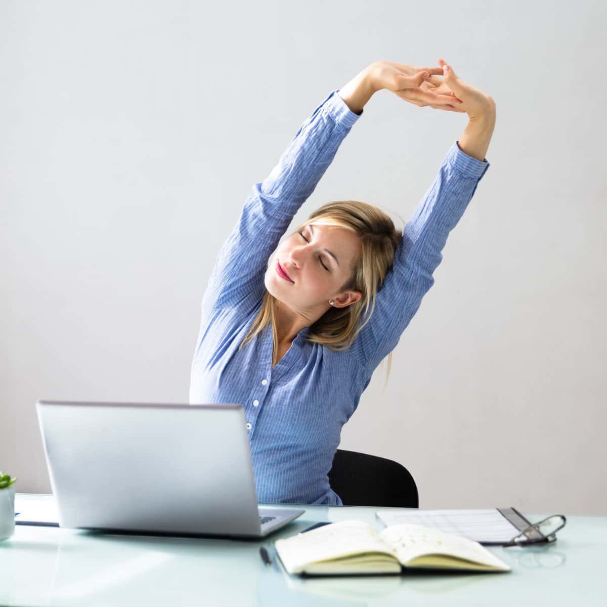 Image of someone stretching while at their desk.