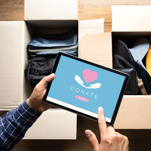 person confirming a donation on their ipad above boxes of clothes they are donating