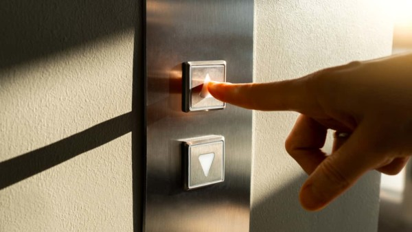 Image of someone pushing elevator buttons.