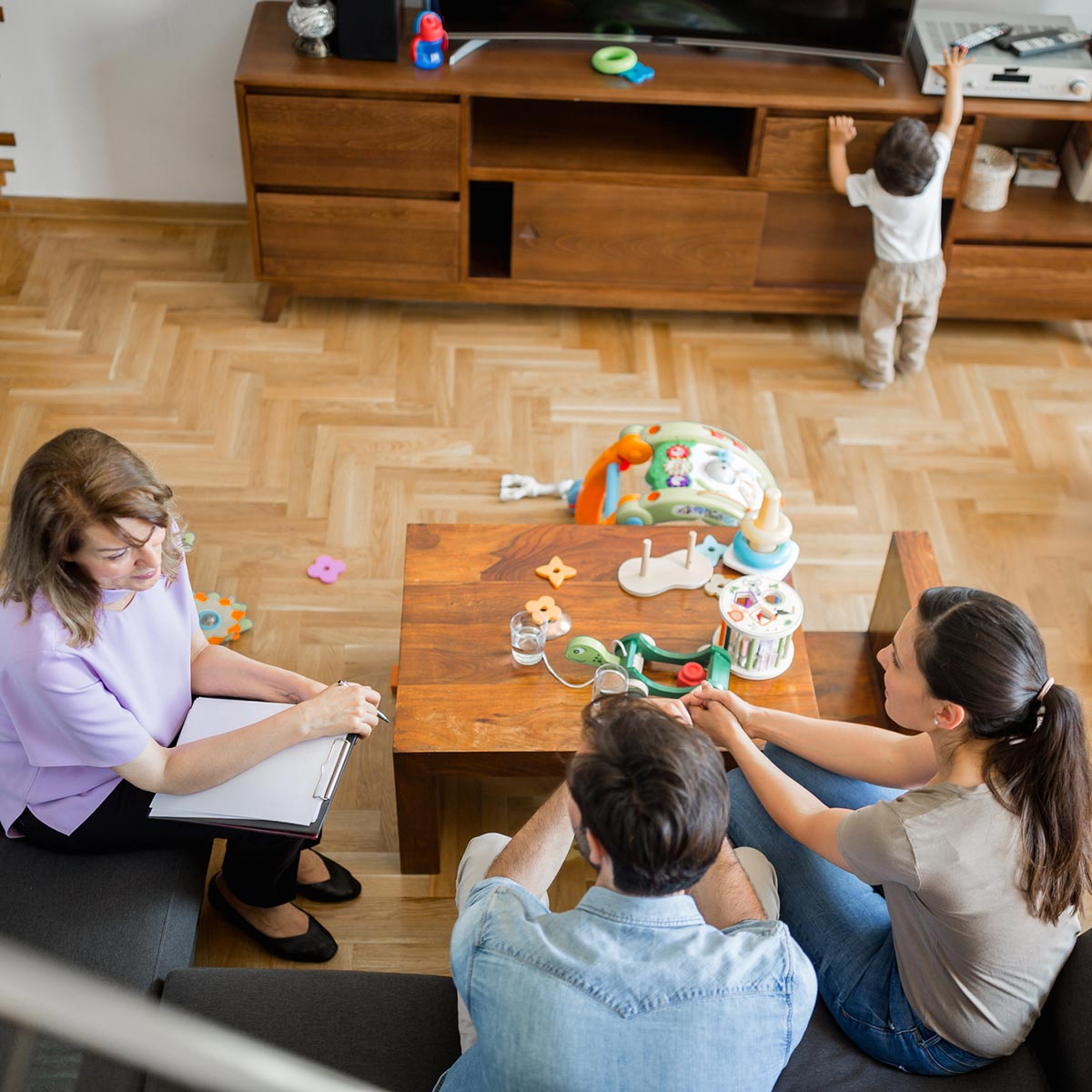 family talking while kid plays with toys and reaches for a remote