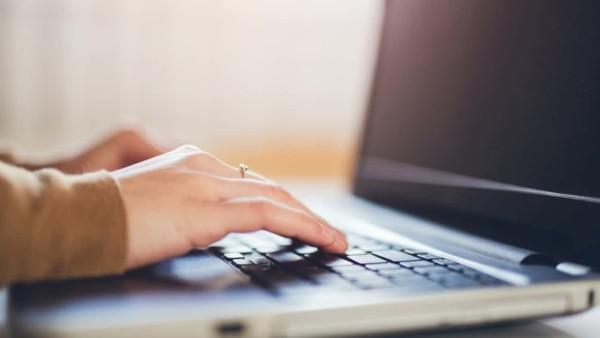 Image of someone typing on a laptop keyboard.