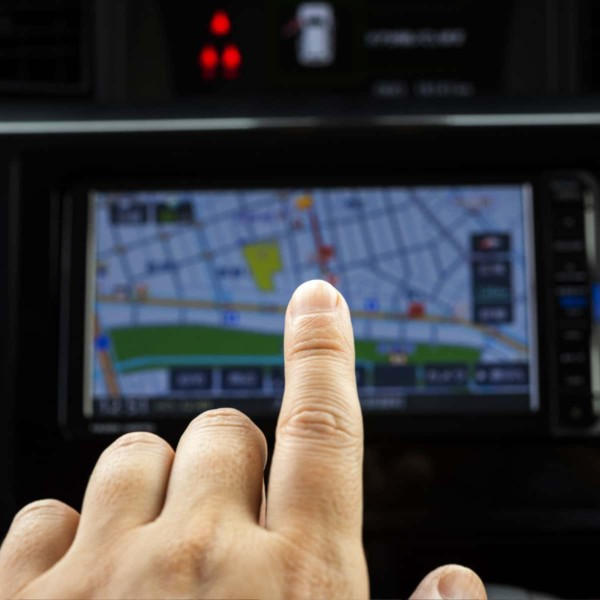 Image of a hand pointing to a gps navigation screen.