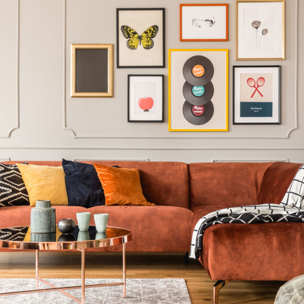 living room with red couch and vertical space used well with wall decor and paintings