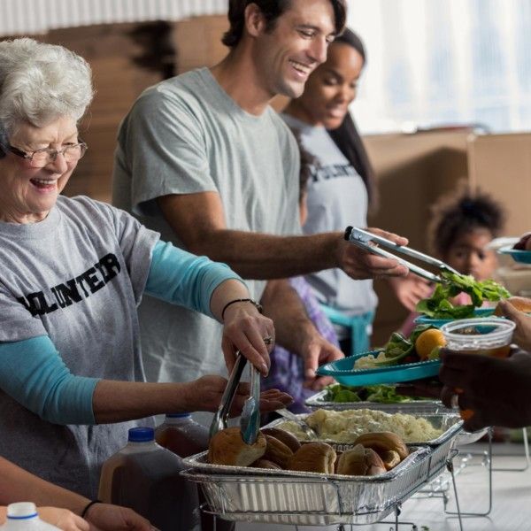 a group of people volunteering by giving out food to people who need it
