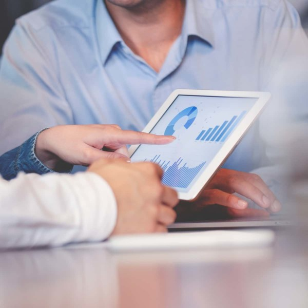 Hand pointing at graphs on tablet during meeting
