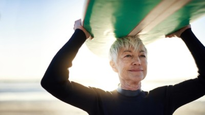 Image of someone holding a surfboard over their head.