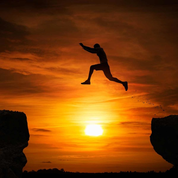 Image of someone who appears to be jumping from one cliff to another.