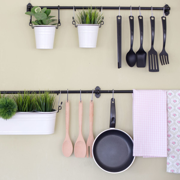 hanging pots and pans on floating shelves on kitchen wall