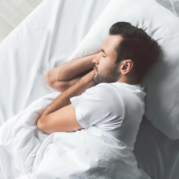 Image of someone laying in bed asleep.