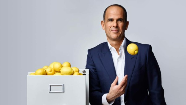 Image of Marcus Lemonis standing next to a file cabinet filled with lemons.