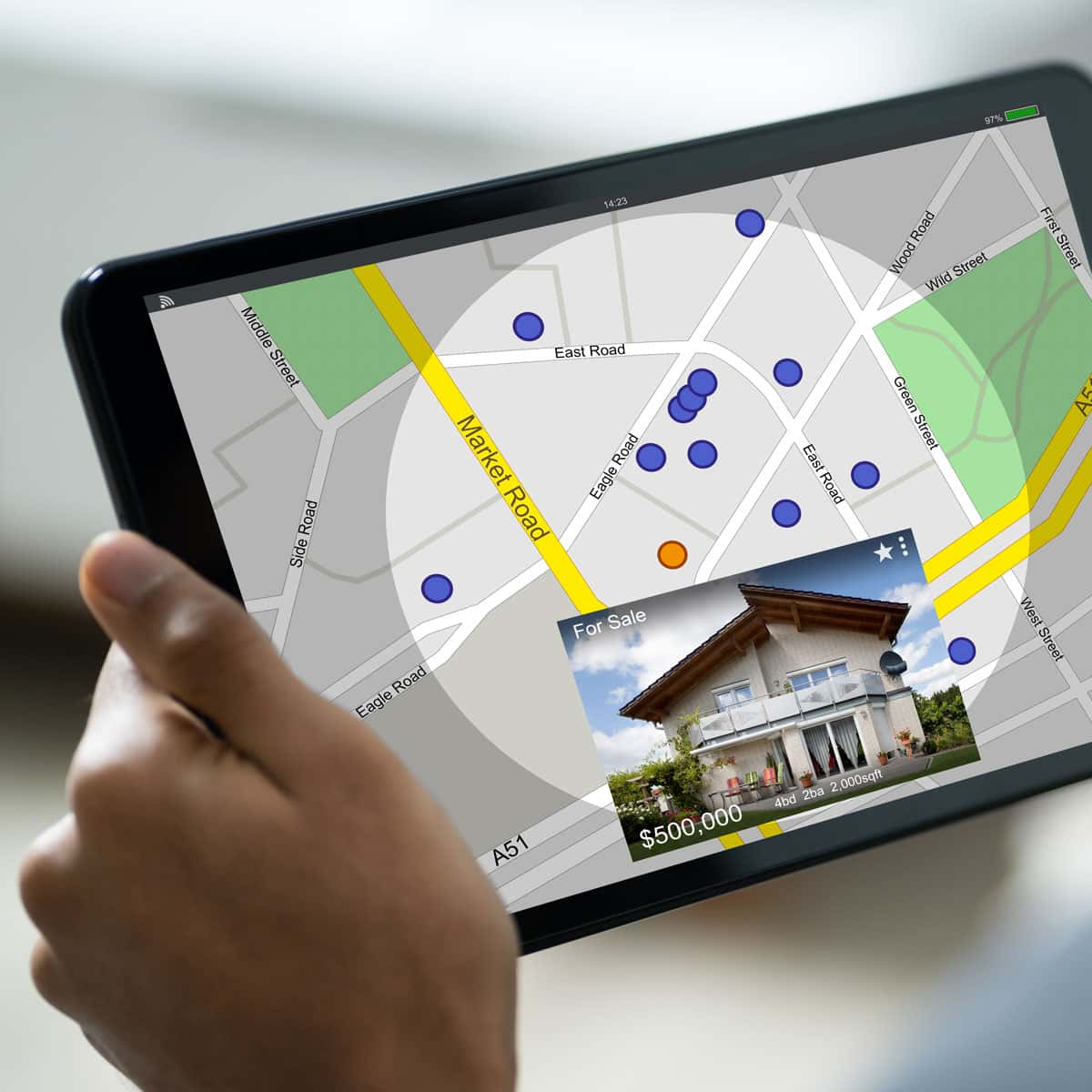 Someone using a tablet to look at houses in the area on a map