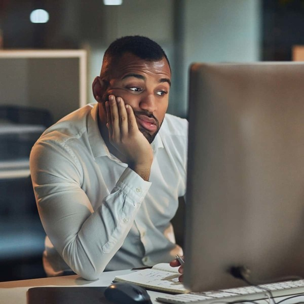 Man frustrated sitting at computer doing work