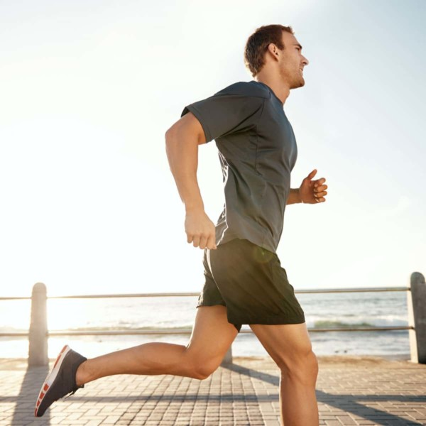 man running along the beach on the boardwalk