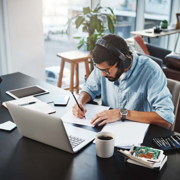 man working at his desk at home with coffee