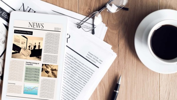 Image of a news article on a table next to a cup of coffee.