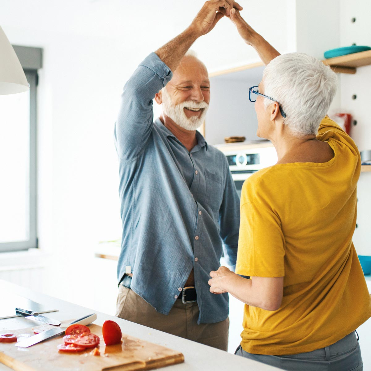 Older couple dancing in the kitchen while cooking