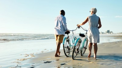 Older couple walking their bikes along the beach