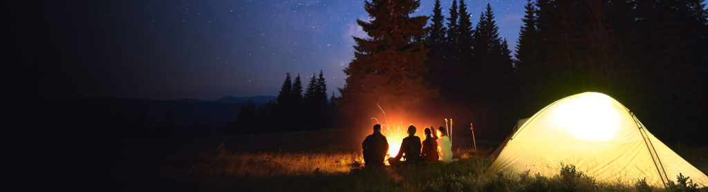 Image of a group of people camping outside at night.
