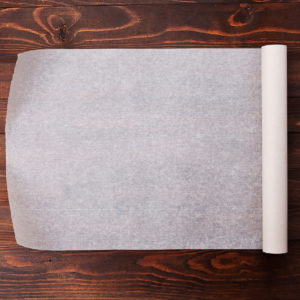 Parchment paper rolled out on a wooden table