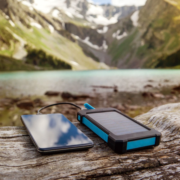 phone charging with a remote charger in front of mountains and a lake