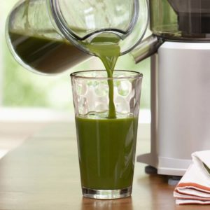 Image of someone pouring cold pressed green juice.