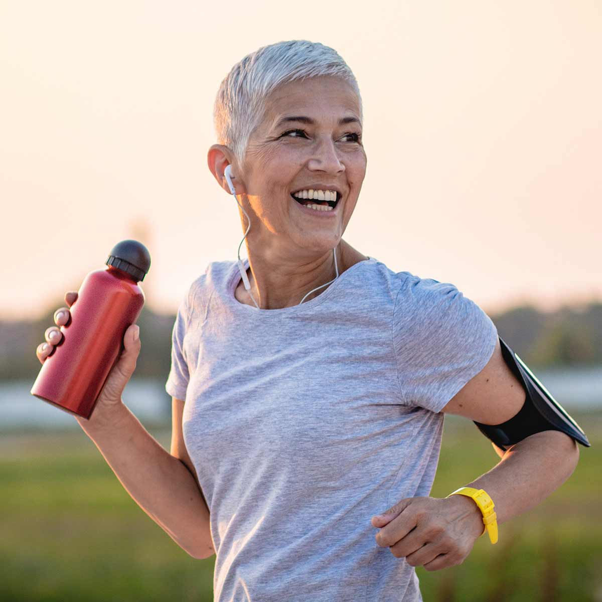 Image of someone running with a bottle of water in their hand and smiling.