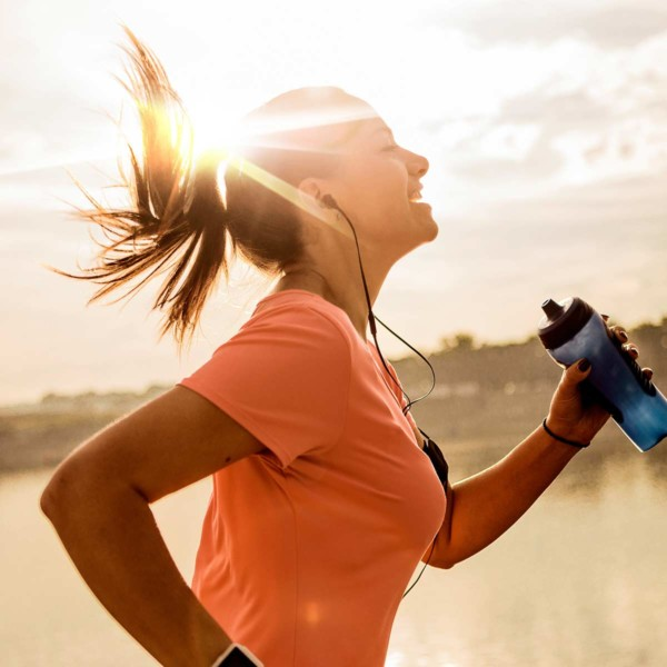 Image of a person running with a bottle of water with the sun in the background.