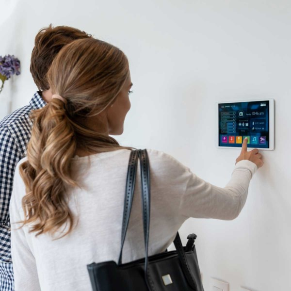Image of people using a tablet with smart home controls mounted to a wall.