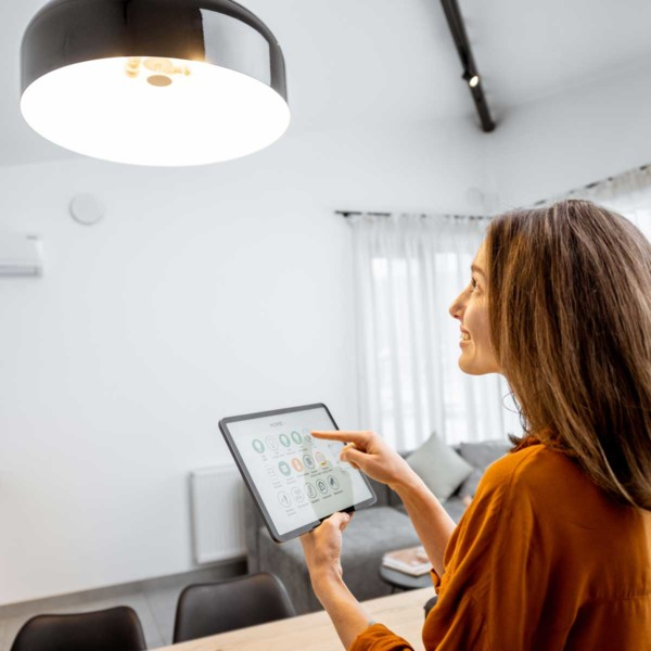 Image of someone controlling the lights in their house with a tablet.