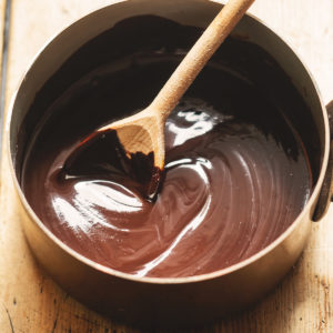 Stirring melted chocolate in bowl with a wooden spoon