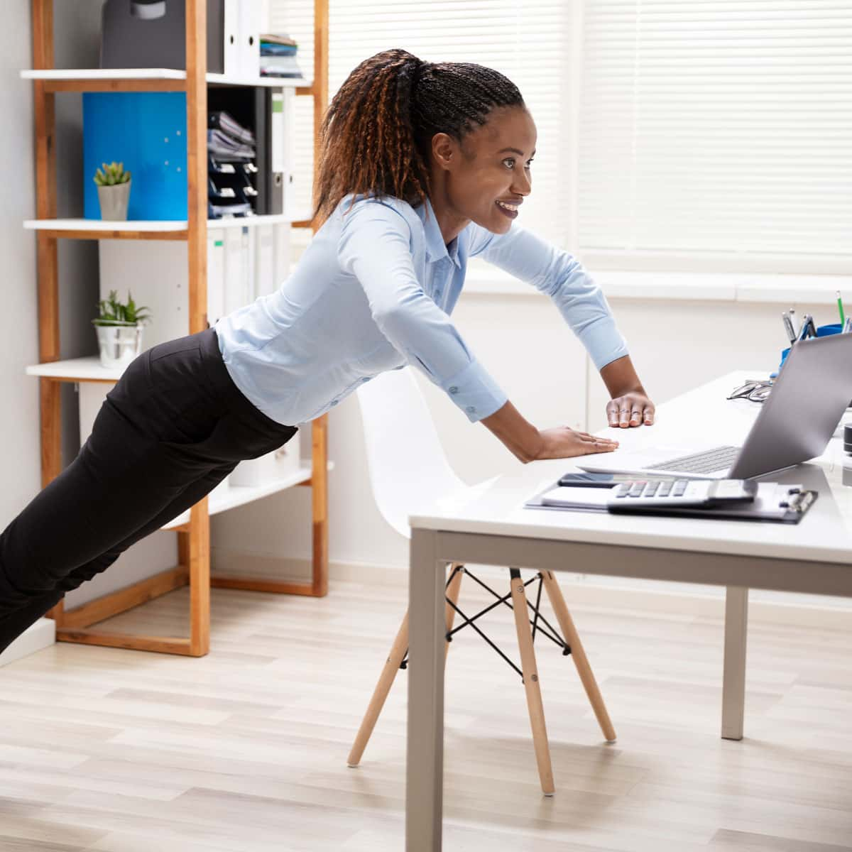 Woman exercising at her desk by doing push-ups