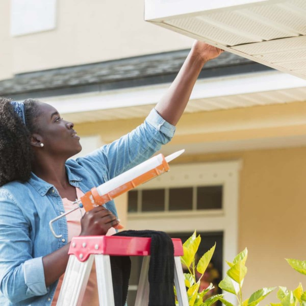 Woman fixing the siding of her house with caulk