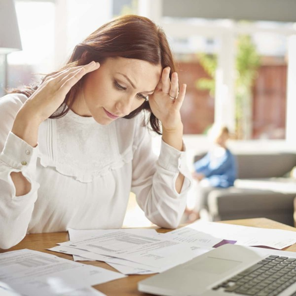 Woman looking at financial papers so she can manage her finances