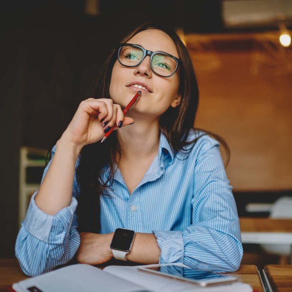 Woman thinking about being self aware with pen in hand