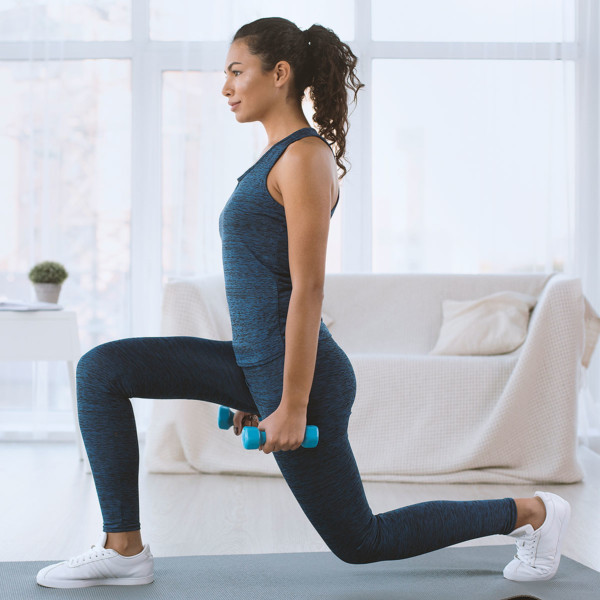 woman on mat at home doing lunges