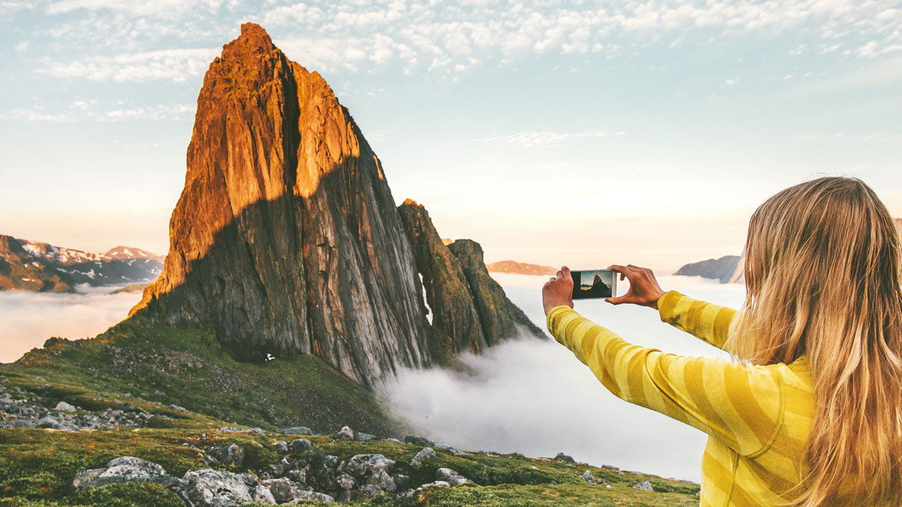 women photographing a mountain surrounded by fog in a yellow shirt