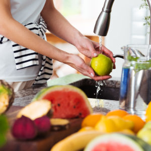 Woman washing green apple in sink before adding to her green juice