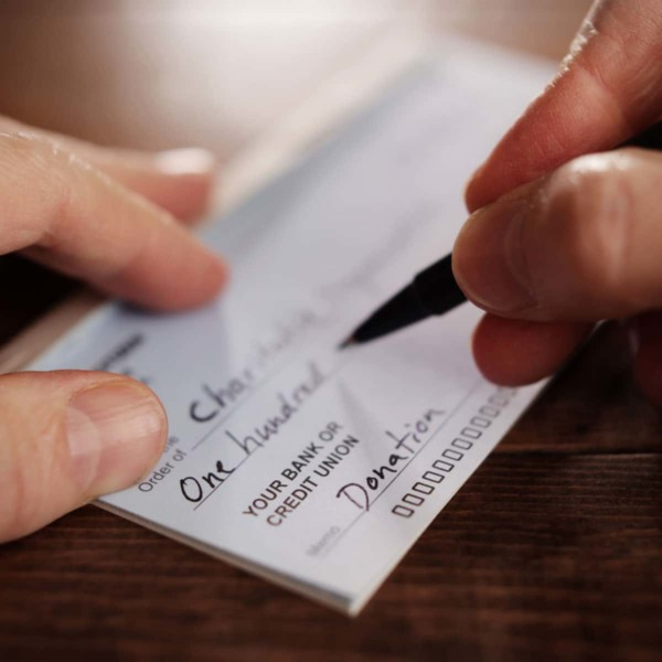 zoomed in image of person writing a check