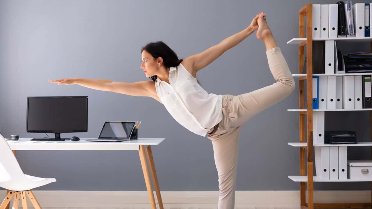 Image of someone doing a yoga pose at their computer desk.