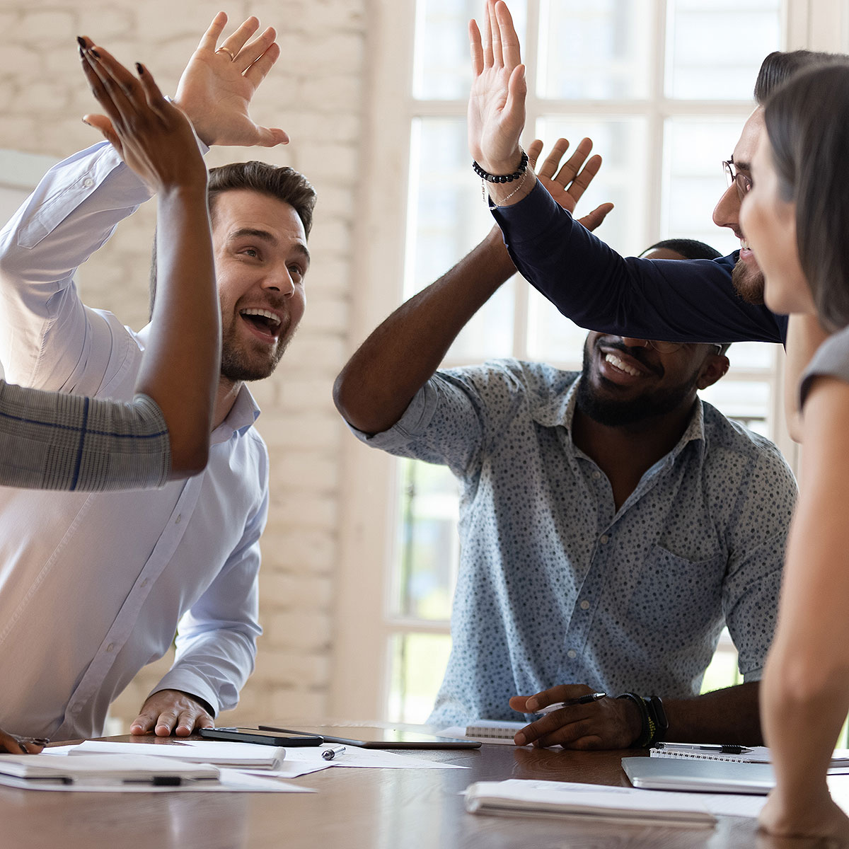 image of friends celebrating success during meeting