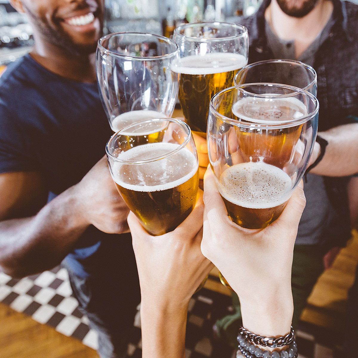 Group of friends hanging out and cheersing beers to celebrate friendship